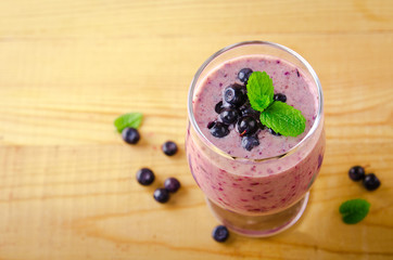 Healthy blueberry banana smoothie with mint and fresh berries in a glass