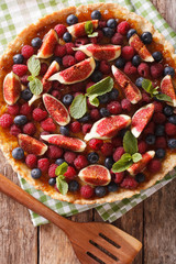 tart with figs, raspberries and blueberries macro. vertical top view