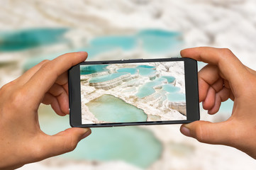 Taking photo of mineral springs Pamukkale with mobile phone