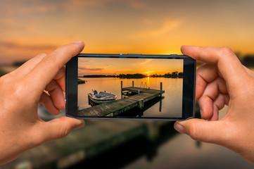 Taking photo of sunset over lake with mobile phone