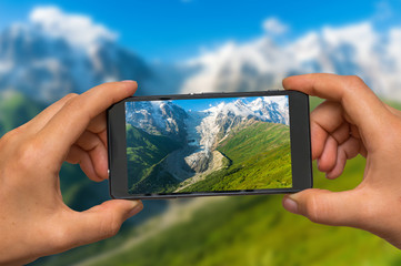Taking photo of mountains and glacier with mobile phone