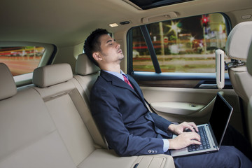 Man with laptop sleepin in a car