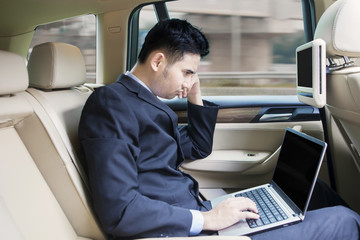 Man working with laptop inside a car