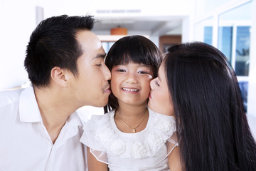 Parents kiss their daughter at home