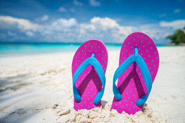 Pink beach flip flop on white sand tropical island