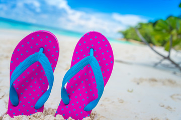 Pink beach flip flop on tropical white sand beach summer holiday