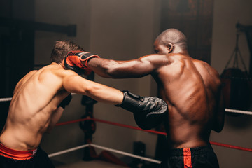 Two boxers fighting in the ring throwing punches