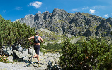 young man without tshirt running with backpack ultra trail race in high mountains with peak view