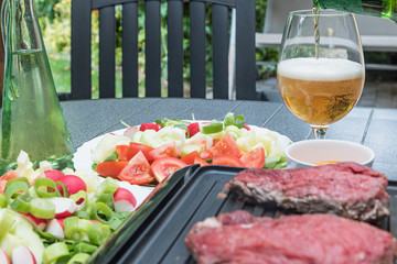 Beef steaks are grilled on an electric stove. The beer is pouring into prepared glass.