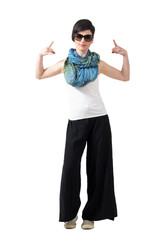 Rocker girl with sunglasses showing devil horns rock and roll sign with both hands. Full body length portrait isolated over white studio background.