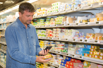 Man reading label on the product in supermarket