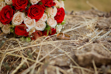 Wedding rings near bouquet of roses