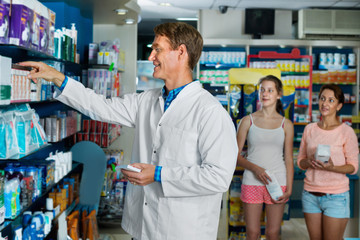 Smiling man pharmacist  working in pharmaceutical shop