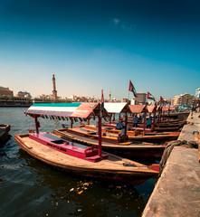 Traditional Abra taxi boats in Dubai creek - Deira during sunny day, Dubai Deira, United Arab Emirates