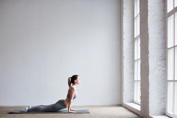 Woman exercising yoga indoors.