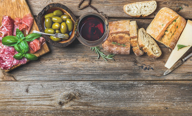 Wine snack set. Glass of red wine, green mediterranean olives, prosciutto, salami and aged cheese over rustic wooden background. Top view, copy space, horizontal composition