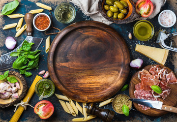 Italian food cooking ingredients on dark plywood background with round wooden tray in center, top view, copy space, horizontal composition