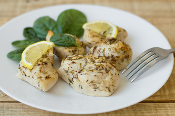 Baked chicken fillet with lemon slices and spinach leaves on a white simple plate