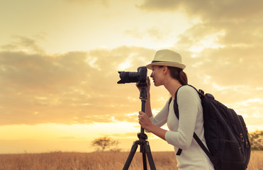 Female photographer taking pictures outdoors. Travel and adventure concept.