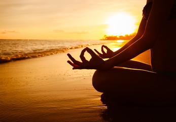 Woman meditating on the beach.