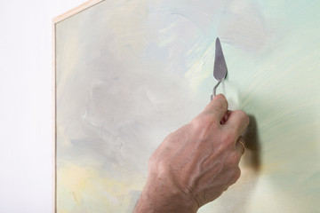 An artist painting with a palette knife in studio