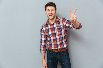 Handsome young man showing victory fingers sign