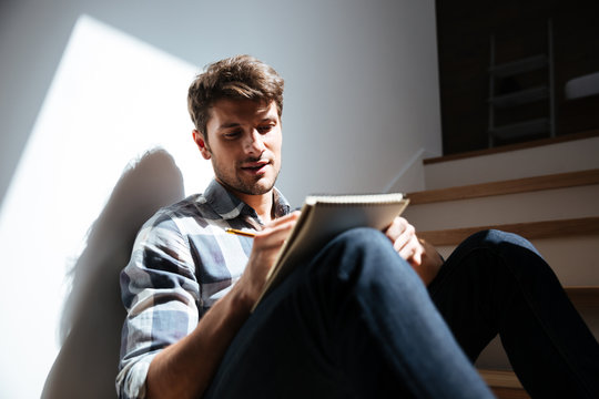 Man sitting on stairs at home and writing in notepad
