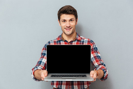Smiling young man in checkered shirt holding blank screen laptop