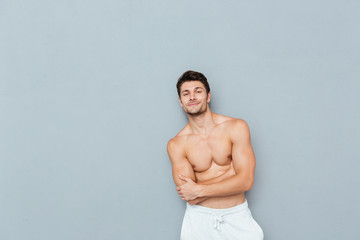 Smiling confident shirtless young man standing with arms crossed