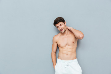 Attractive shirtless young man standing and posing