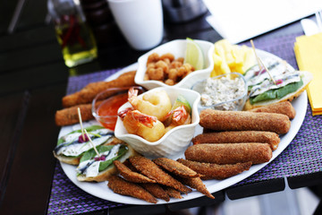 Nibbles sharer plate. King Prawns, Baby shrimps in bread crumbs, anchovies on toast bread ,fish fingers, crab sticks in bread crumbs,sardines in bread crumbs.At the restaurant .