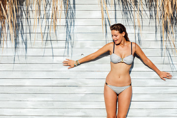 sexy woman in bathing suit standing on wooden vintage wall with