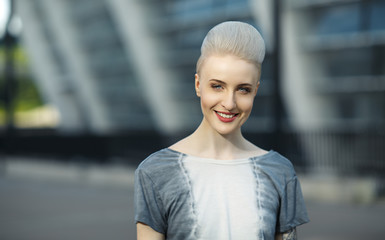 Portrait of smiling hipster girl with blonde mohawk behind