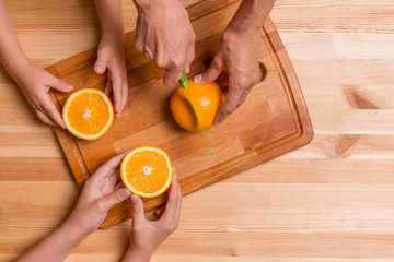 Mother cuts the orange on wooden board to their children