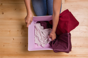 Girl in jeans gets clothes from pink boxes