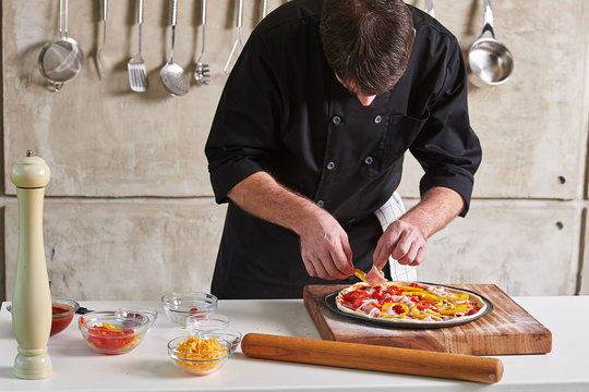 Restaurant hotel private chef preparing pizza adding toppings