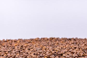 Ein Haufen aus gerösteten Kaffeebohnen auf weißem Untergrund