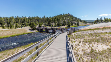 Wooden bridge across the Firehole River. Amazing scenery at Midway Geyser Basin, Yellowstone National Park, Wyoming