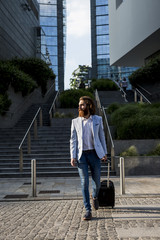 Stylish businessman walking with suitcase outdoors