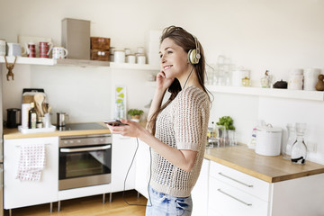 Smiling young woman in kitchen listening to music