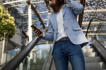 Stylish businessman using cell phone on escalator