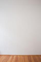 Weiße Wand und Holzfußboden - Freiraum für Text und Bild