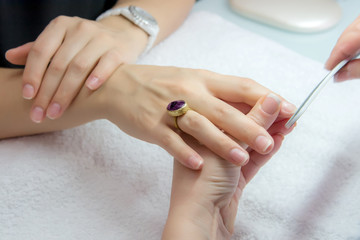 Woman hands in a nail salon receiving a manicure by a beautician