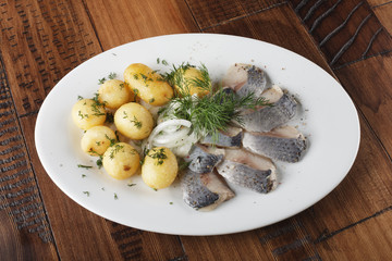 Herring fish with young potato on white plate. wooden background.