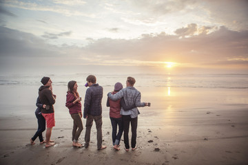 Group of friends looking at sunset on beach