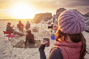 Group of friends having picnic on beach at sunset