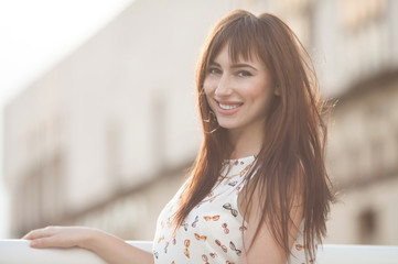 Young smiling woman outdoors portrait. Soft sunny colors. Outdoor closeup fashion portrait of young pretty woman in summer meadow.