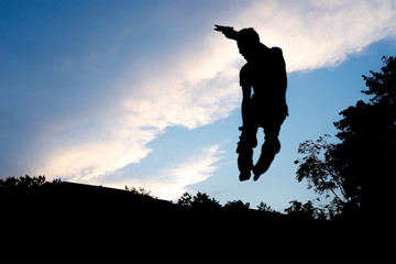 silhouette of a skater in a jump against the blue sky