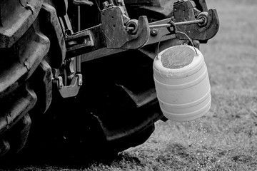 Wall Mural - Detail of a large tractor wheels with hanging bucket. Black and white photo.