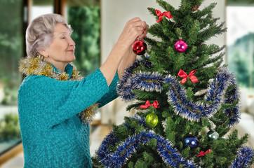 Stunning old woman decorating Christmas tree